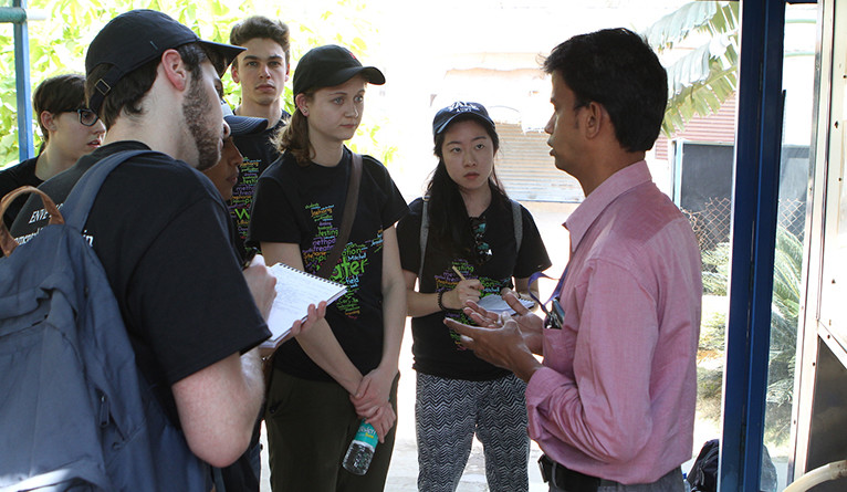 An outdoor group of students listening to a man in a pink shirt speak.