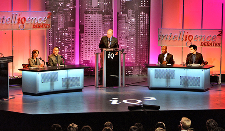 Wendy Kaminer, John McWhorter, moderator John Donvan, Shaun Harper, and Yale professor Jason Stanley on stage at an IQ2 debate.