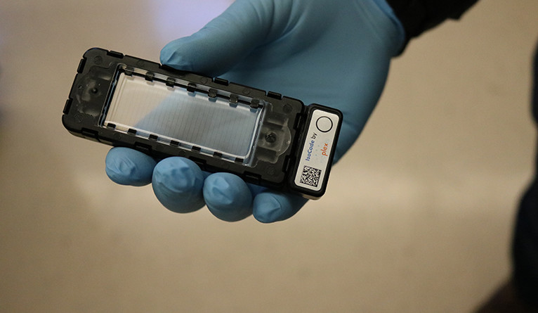 Handheld Isocode Chip being held by someone wearing medical gloves