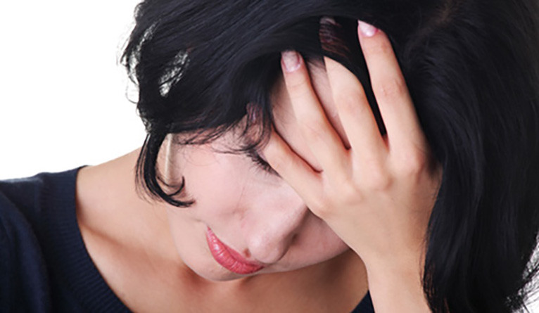 A depressed woman holding her head in her hands.