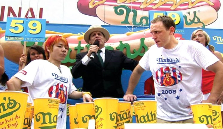 A still from a movie depicting a male and a female at a hot dog-eating contest.