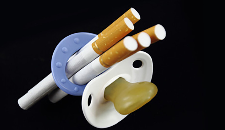 An infant pacifier with cigarettes stuffed through the ring.