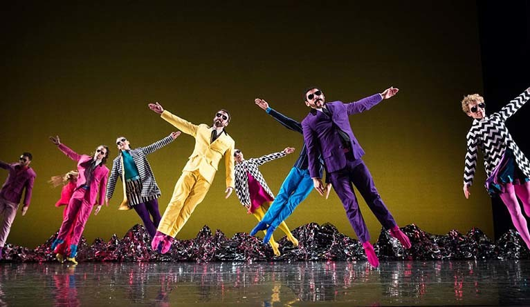 Dancers in multi-colored suits performing the Mark Morris Dance Group's Pepperland