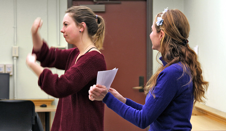 A student using sign language beside her instructor.