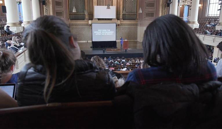 Yale students watch Laurie Santos lecture from the balcony of Woolsey Hall.