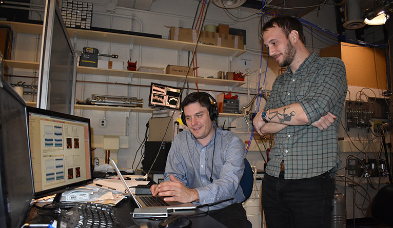 Spencer Topel and Kyle Serniak in the quantum labs in Becton Center listening to the first sound the quantum computer made