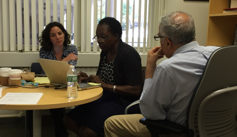 Tracy Rabin, Harriet Mayanja-Kizza, and Asghar Rastegar working in Dr. Rastegar's office