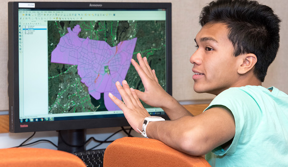 A student gestures toward a monitor showing a highlighted geographic area. (Photo by Karen King Photography)