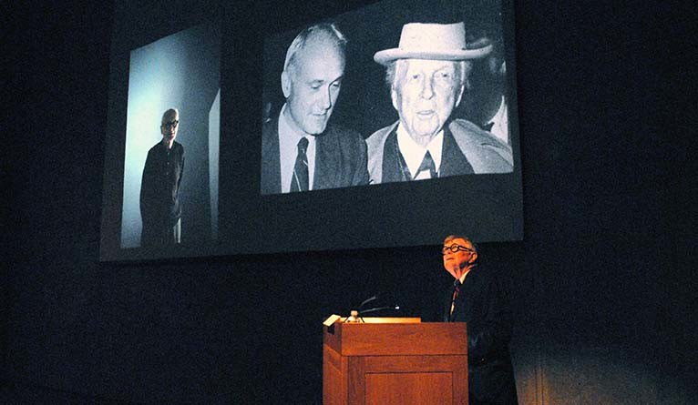 Vincent Scully lectures with photographic slides projected behind him.