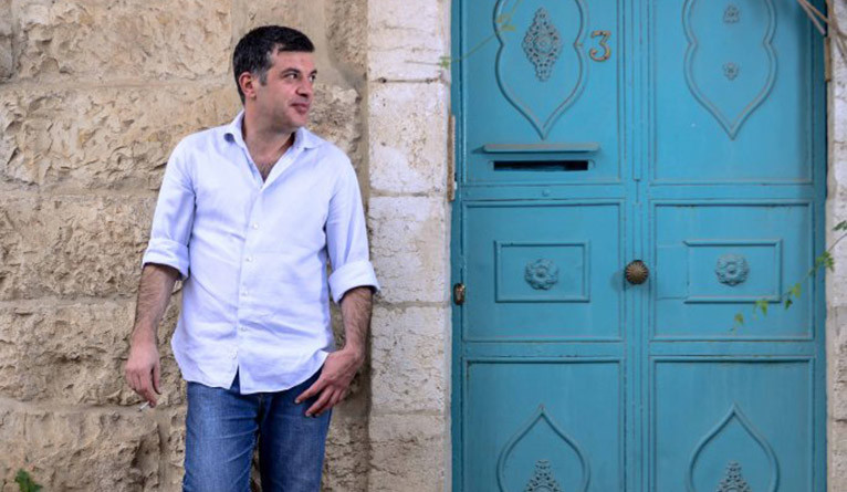 Sayed Kashua posing next to a blue door.