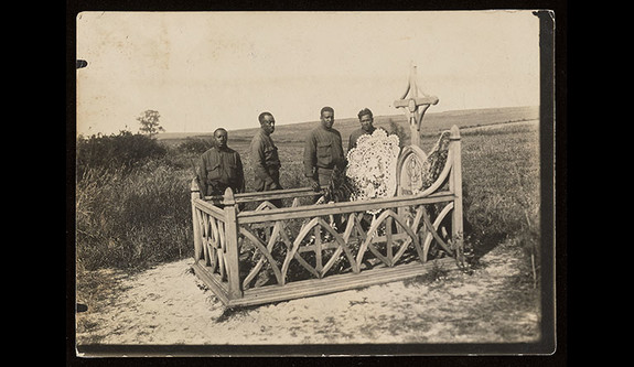 A vintage photo of African American soldiers standing by a grave after World War I.