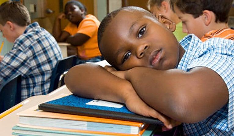 A glum boy resting his head on his desk in a classroom.