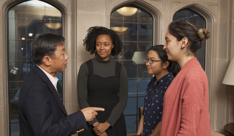 A man in a suit talking to three college students.