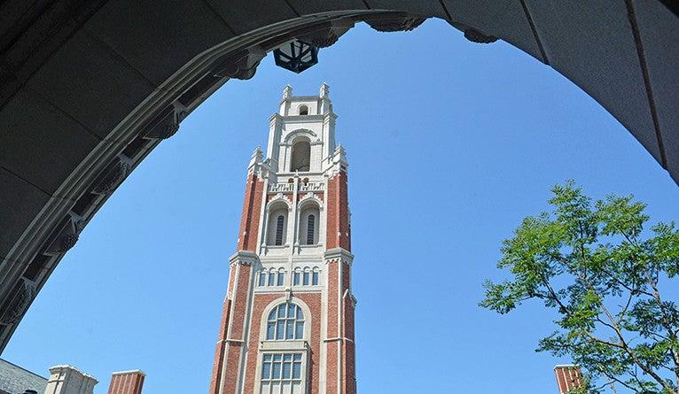 The Bass Tower looms through a gateway.