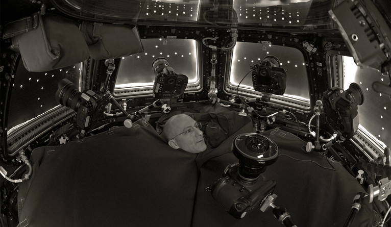 Pettit's head rises from underneath a black canvas used to block light from reflecting off the space station's windows.