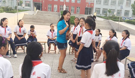 A Yale student stands in a circle of young students, holding a ukelele