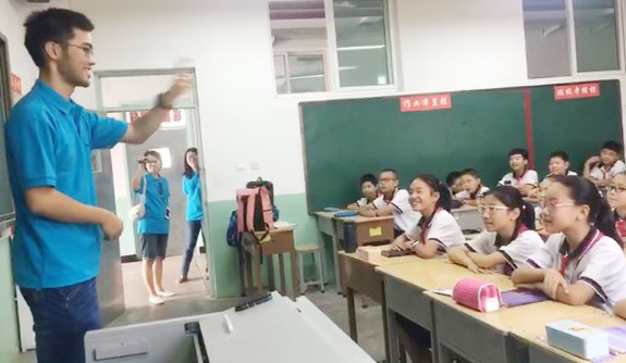 A Yale students stands before a classroom of Chinese elementary school students