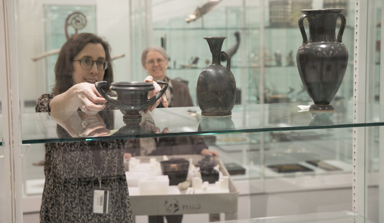 A curator takes an object off a glass shelf while another looks on.