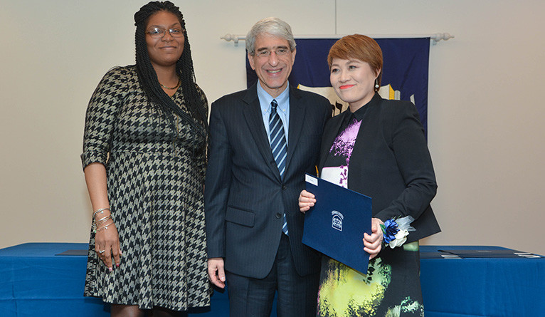 Xia Feng is presented with the Elm Award by Tyisha Walker-Myers and Peter Salovey.
