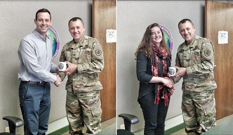 U.S. Army Col. Paul Riley of the Joint Chiefs of Staff presents members of the Yale team with commemorative coffee mugs.