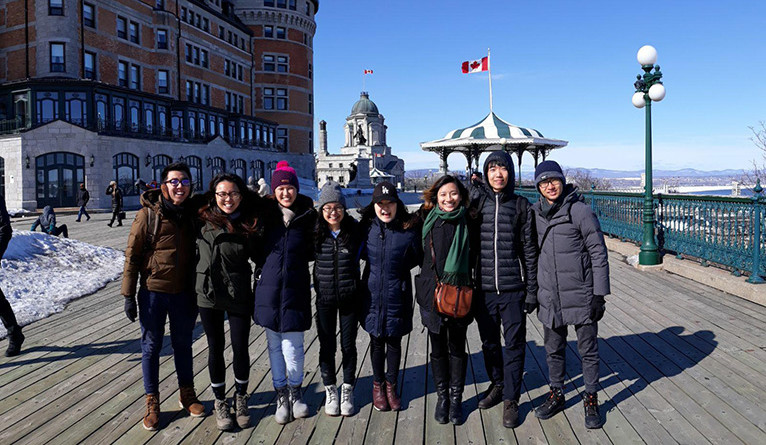 Yejin Park and other Yale-NUS students posing in front of the Canadian flag on a Montreal port.