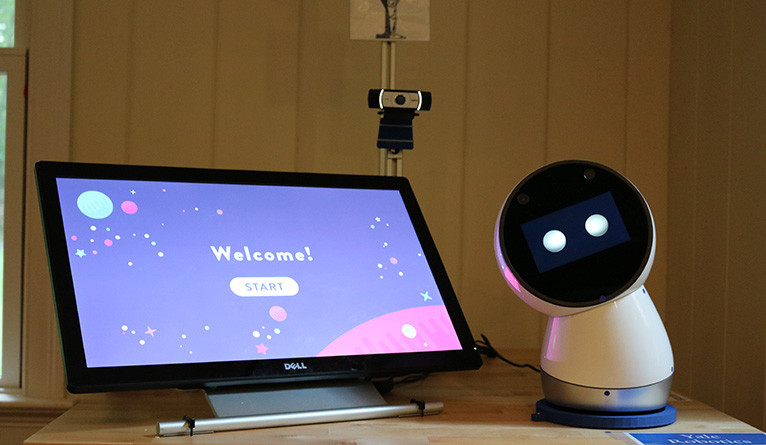 Social robot in the Yale Robotics lab, hooked up to a tablet with a game welcome screen displayed