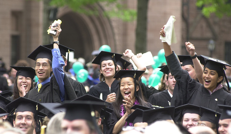 Yale students in caps and gowns cheering at graduation.