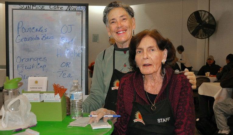 Two women posing beside a dry erase board with a breakfast menu.