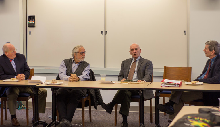 Four people seated at a table during a panel discussion.