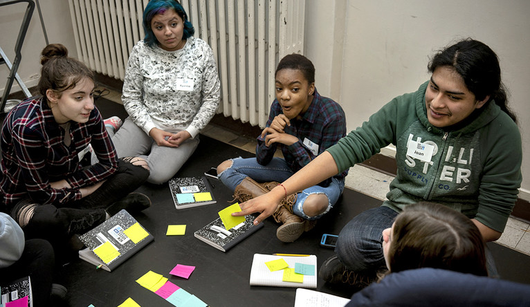 Students passing post it notes — and laughing — during a playwrighting workshop