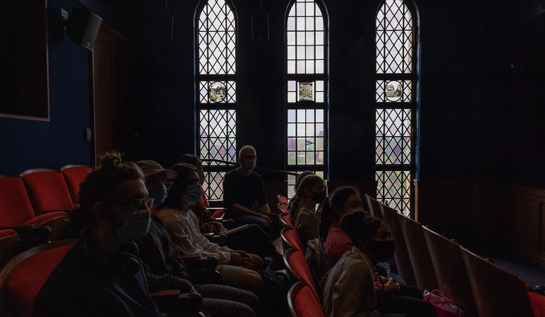 A group of people dimly lit by the screening room's leaded glass windows.