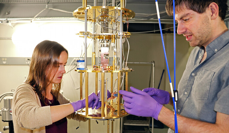 Two people working on scientific equipment.