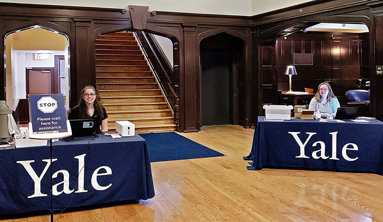 "Two women sitting at separate tables, displaying large ""Yale"" signs."