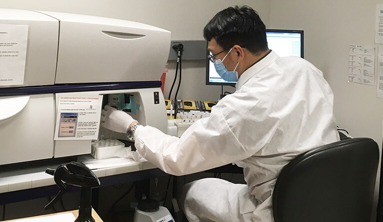 Yale researcher in the lab, wearing a face mask