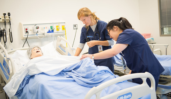 Two nursing students tending to a simulation manikin in a hospital bed.
