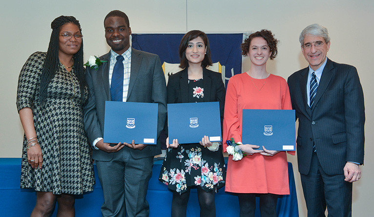 "Robert Rock, Tehreem Rehman, and Kayla Ringelhelm receive the ""Graduate Ivy Award"" on April 25."