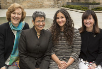 Four female faculty members pose near the Women's Table
