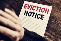 A man finding an eviction notice on his door.