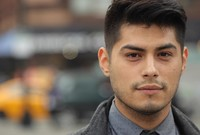 A portrait of a young Latino man on a city street.