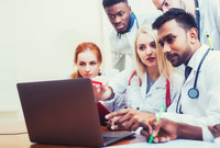 An ethnically diverse group of male and female medical students looking at a laptop.