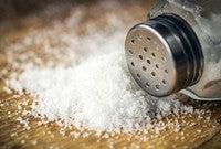 A salt shaker spilled on a wooden table.