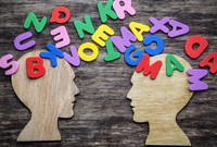Wooden head silhouettes with scattered letter tiles between them.