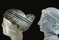 Sculptures of the heads of two women from ancient Mesopotamia.