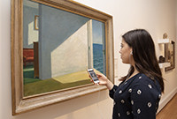 A young woman looking at a painting in an art gallery while listening with earphone to a phone.