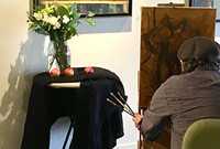 An artist painting a vase and flowers.