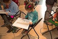 Children seated at desks painting artworks.