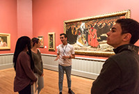 A young male guide in front of artworks  at the Yale Art Gallery talking to three people..