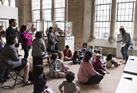 Children standing and sitting in an art museum listening to a teacher.