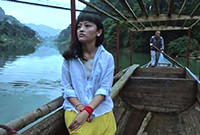 A still image from a film depicting an asian female in a boat on a river.