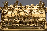 A gold-colored typewriter with miniature soliders in different poses upon it.